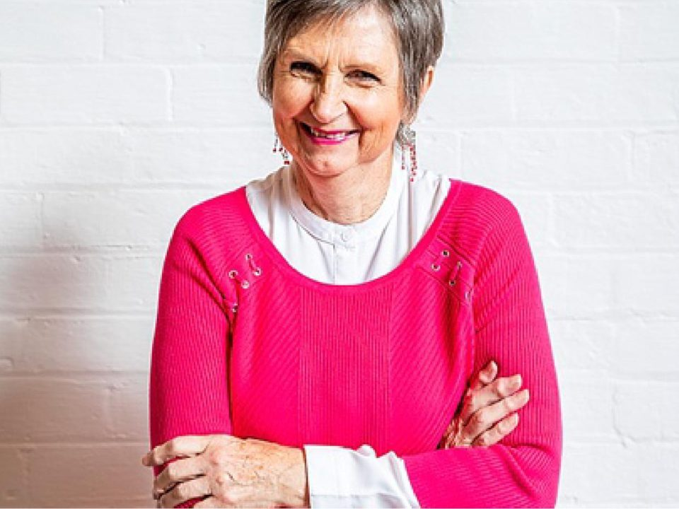 Older lady in a pink sweater with her arms crossed smiling.