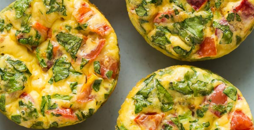 Overhead image of baked egg frittatas with small pieces of spinach and tomato throughout.